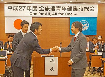 開催地決定後に握手する群馬と石川の県部長
