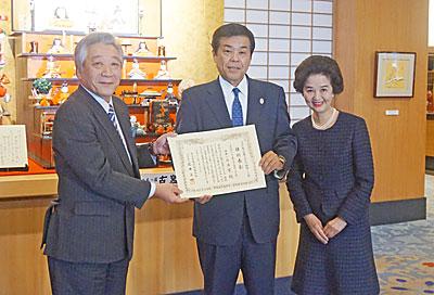 石井社長(左)から佐藤社長(中央)へ表彰状を手渡した